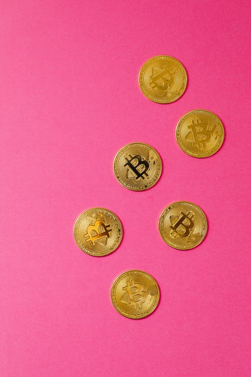 Silver Round Coins on Pink Surface