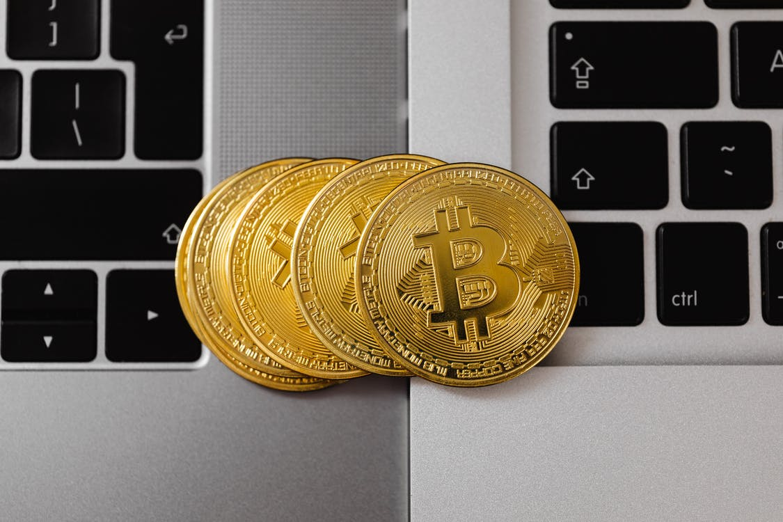 Gold Round Coin on Gray Laptop Computer
