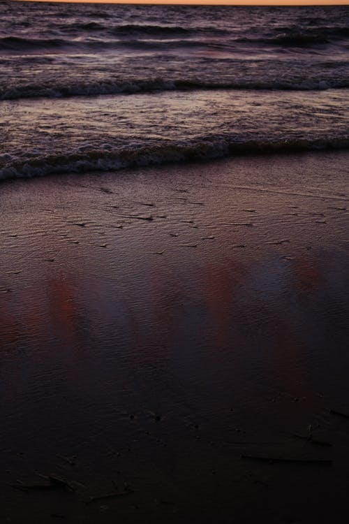 Sandy seashore with waterdrops and endless waving ocean in nature on evening time in tropical resort at sunset in summer