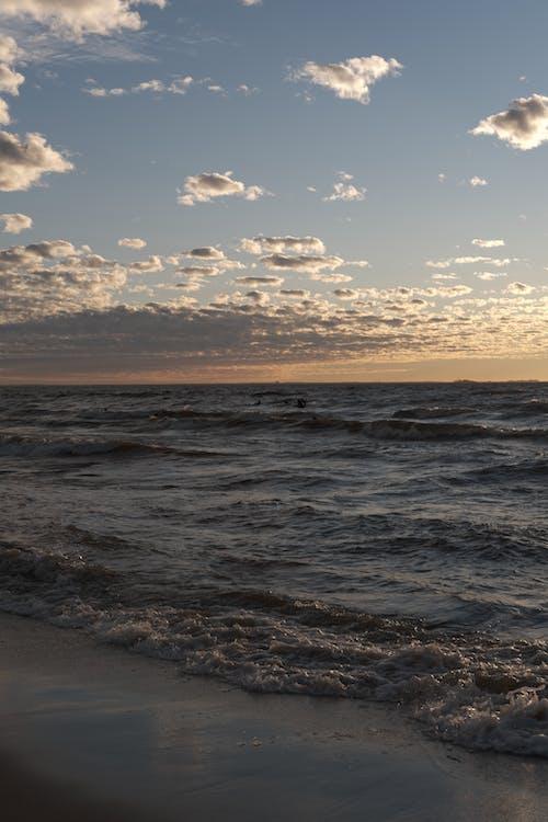 Waving sea against cloudy sky