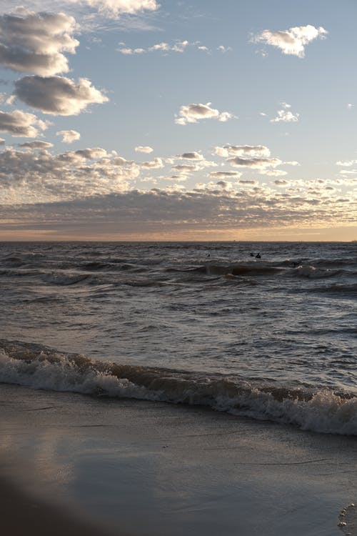 Picturesque sea with waves under cloudy sky