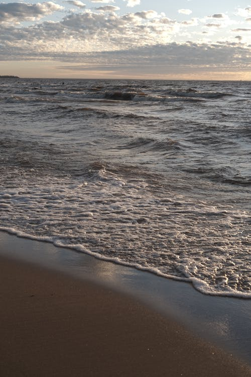Picturesque wavy ocean washing sandy shore under bright sky with cumulus fluffy clouds