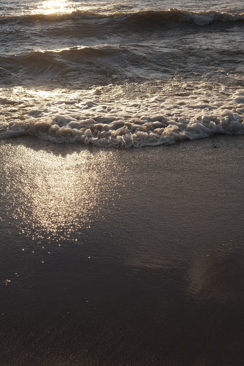 Splashing waves of clean water of sea washing sandy shore in bright sunlight in summer