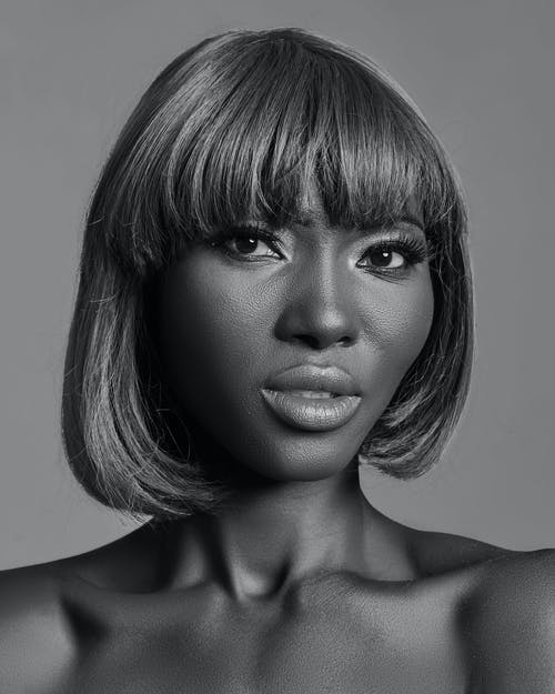 Black and white of African American female with light makeup and bare shoulders standing in studio and looking at camera