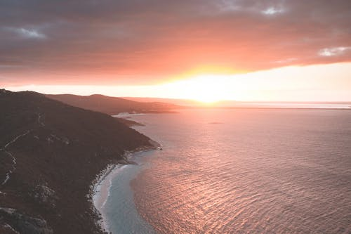 Drone view of calm ocean washing coast with mountain covered with grass against sun shining on horizon of cloudy sky at sunset time