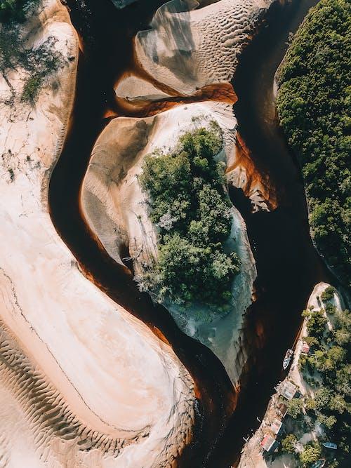 Brown river flowing through sandy coast in tropical resort