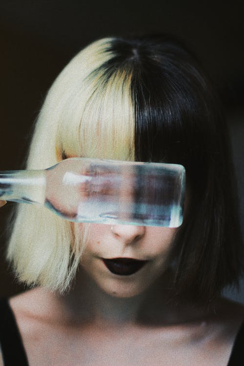 Young female with modern hairstyle and makeup hiding eyes behind bottle of water while standing in dark room