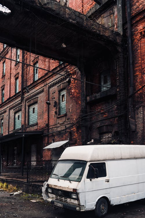White Van Parked Beside Brown Concrete Building