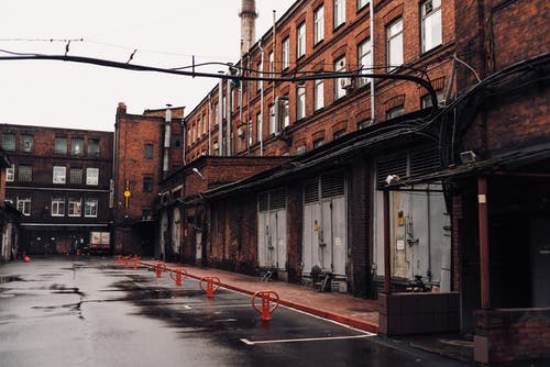 Empty Street Between Brown Concrete Buildings