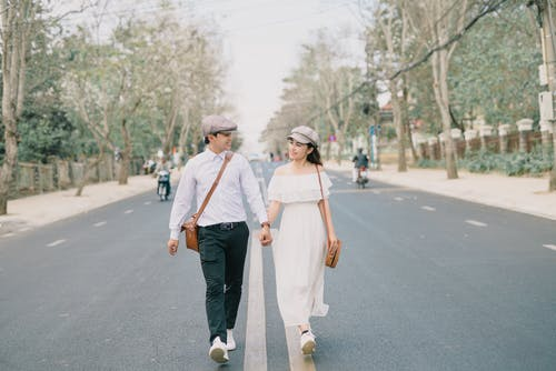 A Couple Holding Hands While Walking on a Street