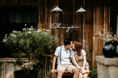 Kissing Asian couple sitting on bench