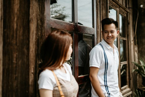 Positive young Asian couple in casual clothes standing near entrance of house with wooden door and glass windows looking at each other
