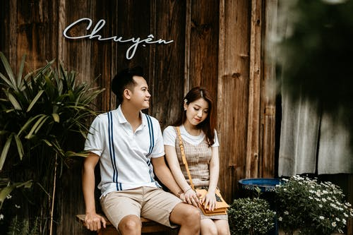 Happy Asian woman with boyfriend sitting on bench