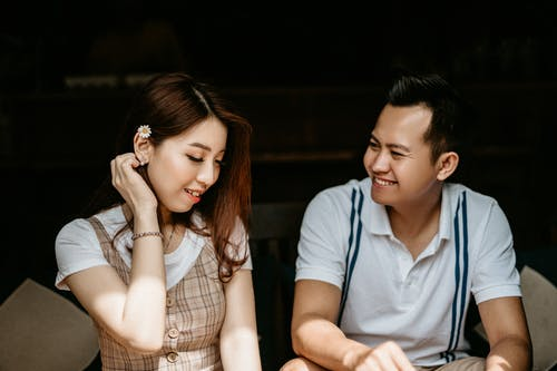 Cheerful Asian couple in casual clothes sitting on sofa having date in cafe and flirting while talking