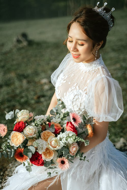 Happy Asian woman in wedding dress in nature