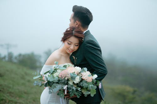 Romantic Asian couple with bouquet of flowers wearing wedding outfits embracing on grassy hill against foggy forest during holiday celebration