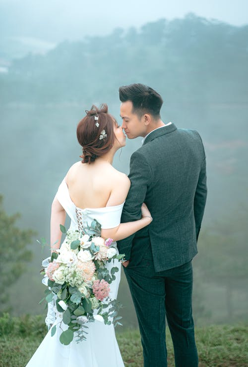 Romantic newlywed Asian couple kissing on hill