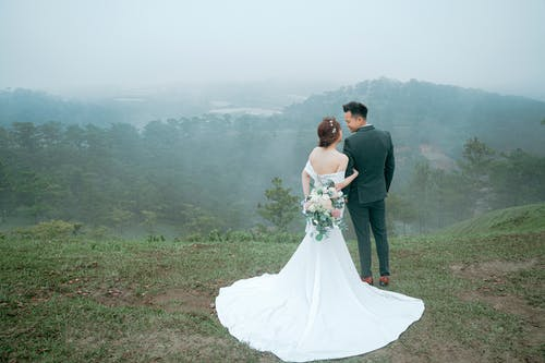 Full body back view of unrecognizable newlywed couple with flowers wearing wedding outfits looking at each other while standing on top of hill above forest in foggy weather
