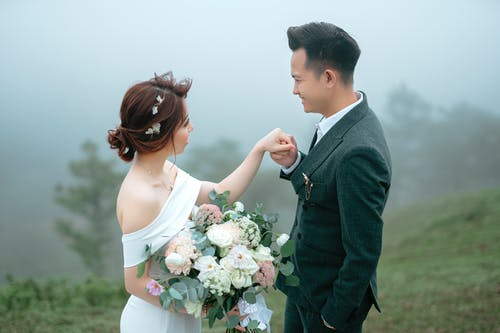 From above side view of positive Asian couple with bouquet of flowers holding hands and looking at each other while standing in nature with trees in foggy weather during wedding celebration