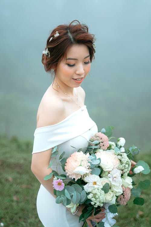 Slim young female carrying wedding bouquet while standing with closed eyes