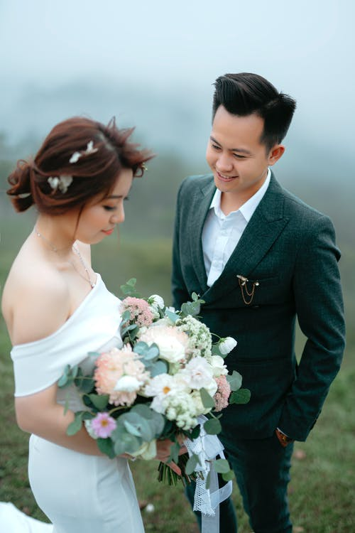 Happy Asian groom wearing elegant suit standing near calm bride carrying wedding bouquet against misty background outdoors