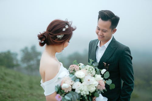 Cheerful young Asian couple  wearing wedding cloth standing close to each other