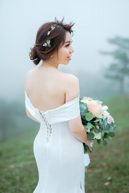 Side view of romantic young Asian bride wearing luxury white dress and holding elegant bouquet standing on misty hill