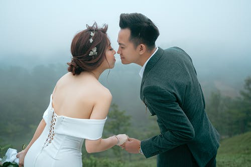 Side view of positive Asian bride wearing wedding dress holding hands while standing close to groom wearing classy suit on slope of grassy hill