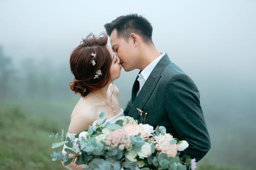 Loving Asian married couple caressing in foggy garden