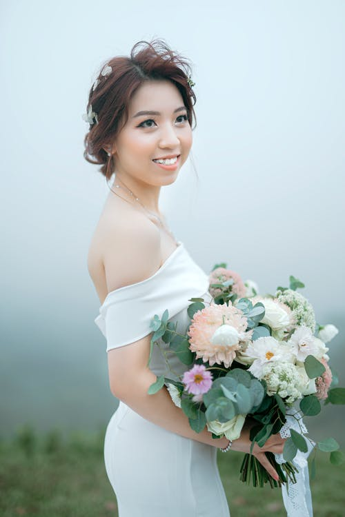 Side view of young Asian woman wearing elegant dress with bare shoulders standing with bunch of flowers and looking away in countryside