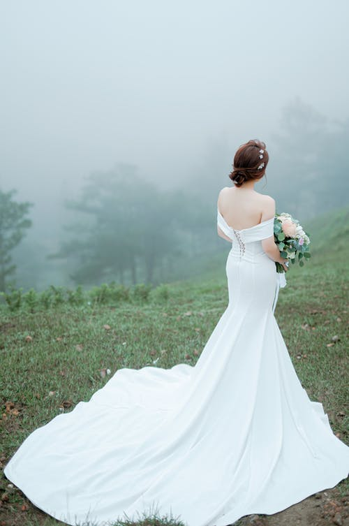 Elegant young lady wearing fancy white dress standing on foggy hill