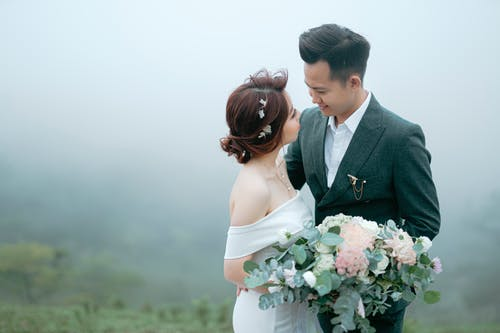Smiling newlywed couple looking at each other while hugging in nature
