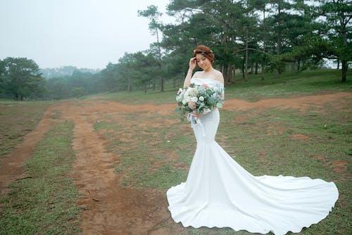 Happy bride with bouquet in park