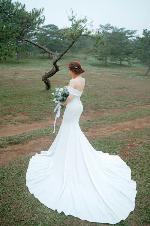 Woman in wedding dress on grassy terrain