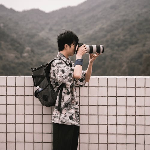 Man in Black and White Floral Hoodie Holding Black Dslr Camera