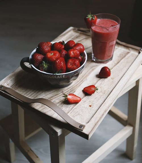 Close-Up Shot of Strawberries on a Metal Bowl beside a Strawberry Smoothie
