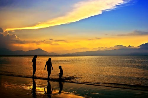 Silhouettes of 3 People in Body of Water during Dawn