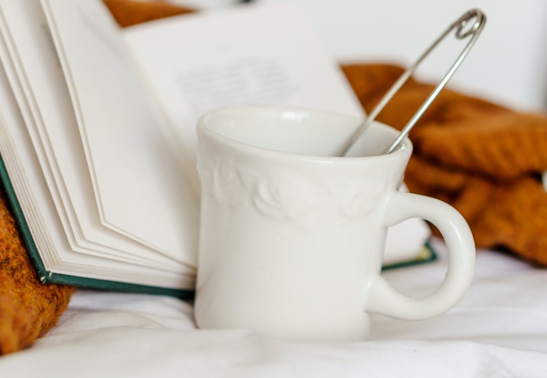 Mug with beverage and book on bed