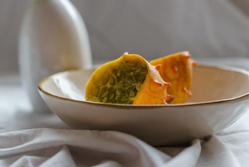 Fresh appetizing exotic fruit in ceramic plate on white blanket at cozy home