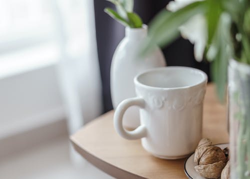 Walnuts near ceramic mug on table in house