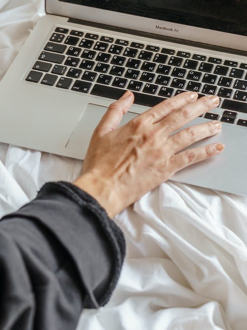 Faceless remote employee typing on laptop on bed