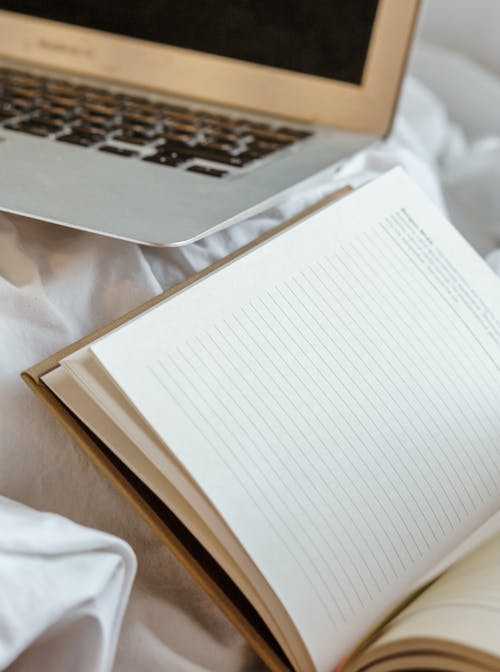 Agenda with horizontal lines near netbook on creased bed sheet in house in daylight