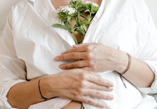 Crop pregnant woman with blooming flower bouquet