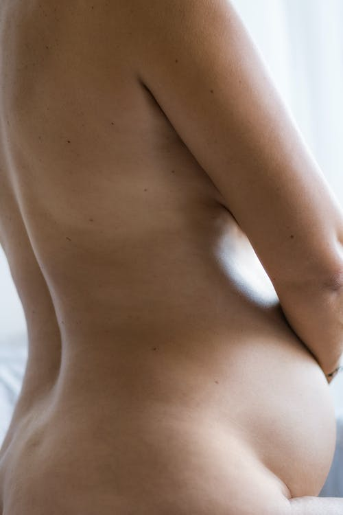 Side view of crop anonymous nude expectant female with curved body stroking belly in daylight