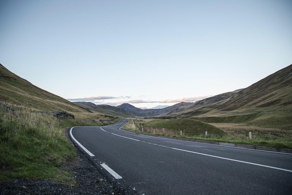 Empty winding asphalt roadway running through grassy hills towards mountain range under blue sky