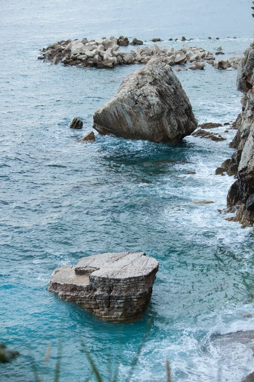 Rocky formations on shallow blue seawater