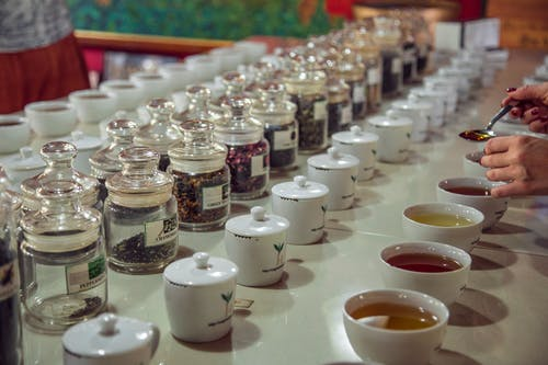 Crop anonymous female with teaspoon standing near table with assorted aromatic teas served for tea tasting session