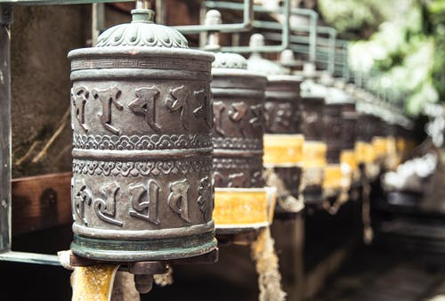 Row of oriental carved prayer wheels located in green Buddhist park on sunny weather
