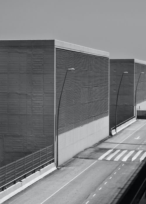 Black and white of concrete constructions with metal grid with fence located near asphalt road with marking lines on street in city
