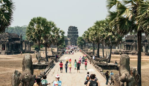 Crowd of people strolling along paved walkway of ancient Angkor Wat in Cambodia
